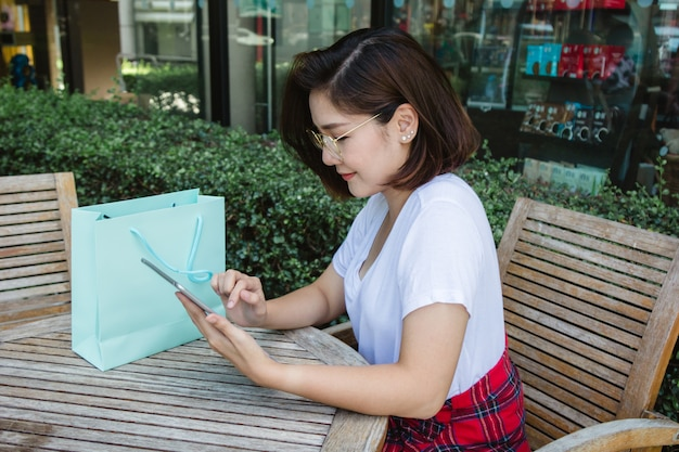 スマートフォンを使ってカフェに座って話したり、読んだり、メッセージを出す朗らかなアジアの若い女性