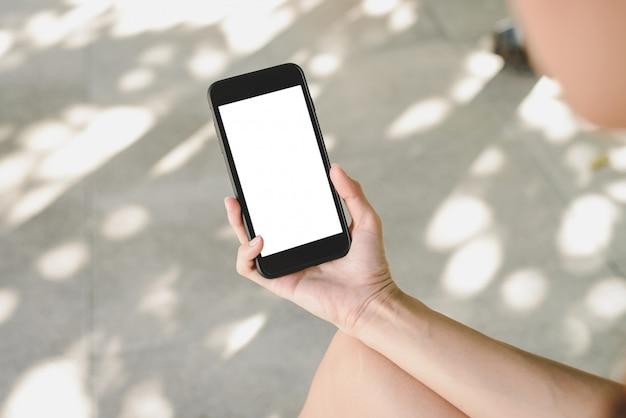 スマートフォンを使用している若いアジア人の女性は、カフェで白い空白の画面をモックします