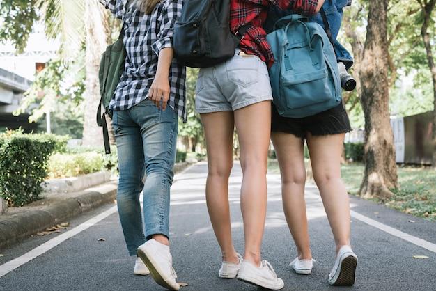 バンコクの都市の公園で旅行中に一緒に幸せに歩いていると感じるアジアの女性のグループ