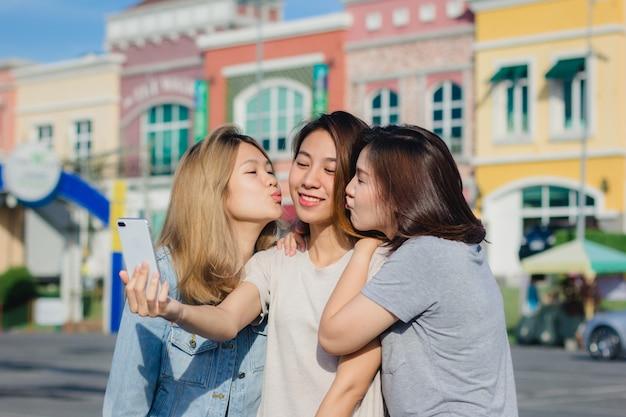 スマートフォンを使用して魅力的な美しいアジアの友人の女性。幸せな若いアジアの十代