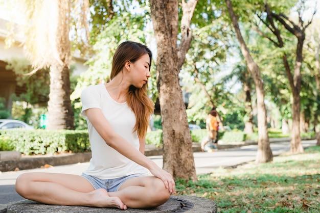 若いアジア人女性のヨガは、ヨガを練習中に静かに瞑想しています。