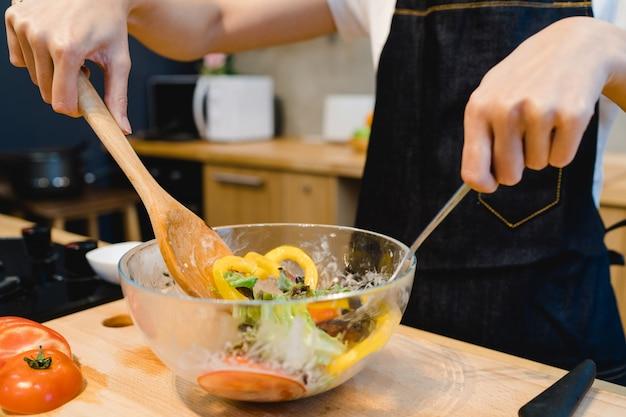 幸せな美しいアジアの女性は、台所でサラダの食べ物を準備する