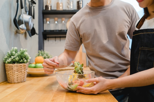 美しい幸せなアジアのカップルは、キッチンでお互いを食べている
