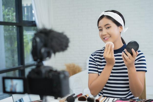 美容ブロガー、現在の美容化粧品、ビデオを録画するためにカメラに座っている間