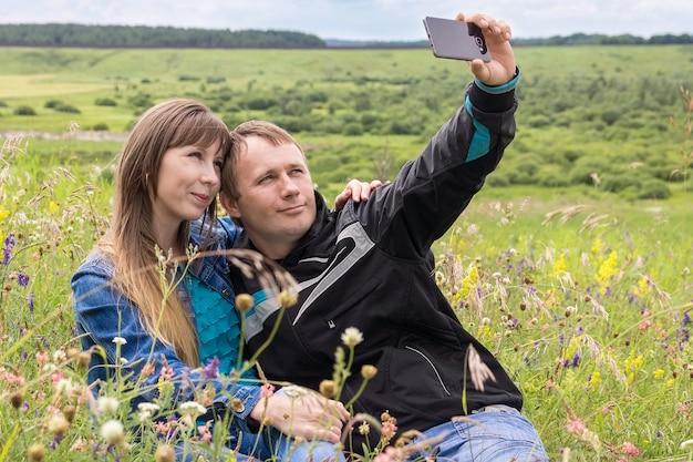 Девушка и мужчина фотографируют себя на телефоне