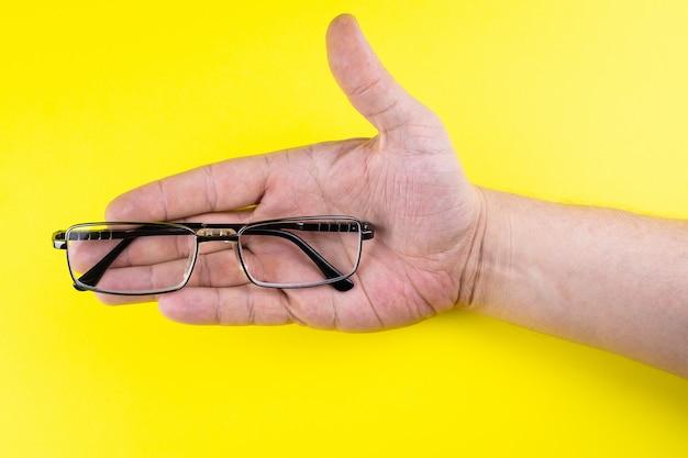 手にメガネ