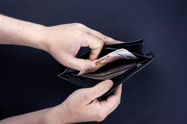 お金で財布を保持している手の平面図