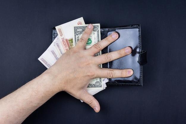 Вид сверху руки, держащей кошелек с деньгами