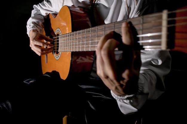 ギタリストの手とギターをクローズアップ。クラシックギターを弾く。ギターを弾く。