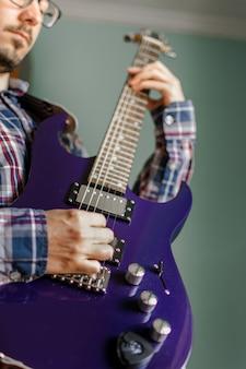 男は自宅でエレキギターを弾くことを学ぶ
