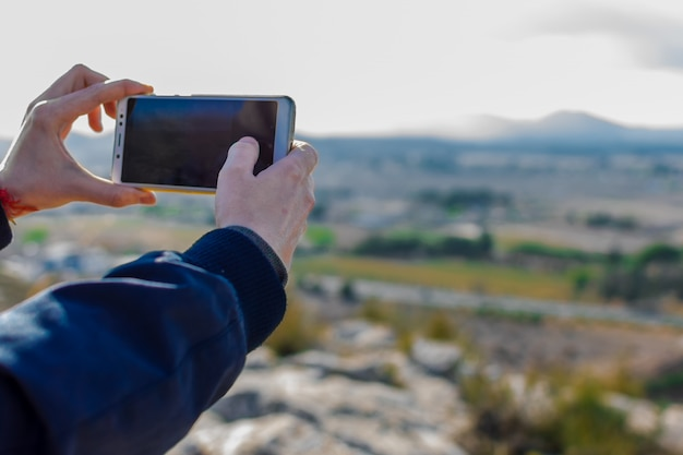 男性の観光客は携帯電話のカメラで写真を撮っています