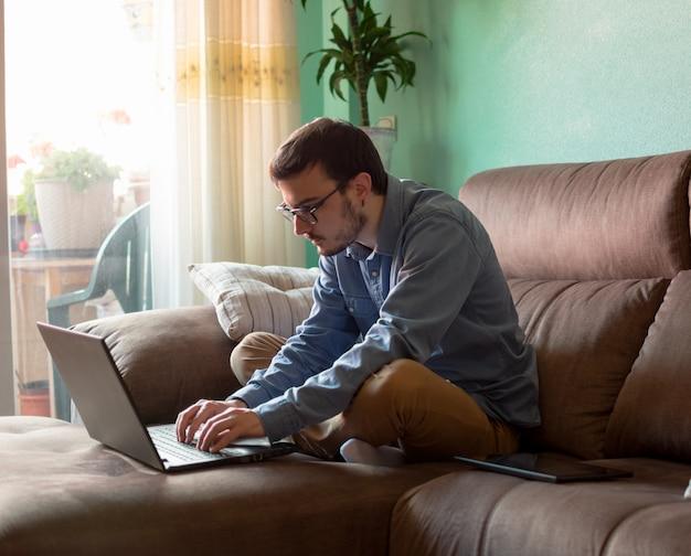 自宅のソファの上のラップトップを持つ若者