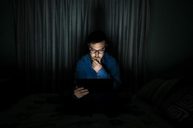 自宅の夜にベッドの上に座っているタブレットでテレビシリーズを見ている男
