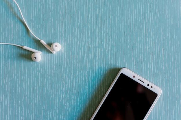 白いヘッドフォンとスマートフォンのトップビュー