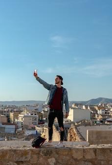 キャップを持つ若者は、バックグラウンドで街と一緒に写真を撮ります。ライフスタイルのコンセプトです。