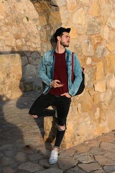 ジャケットとバックグラウンドで城とキャップを持つ若者。ライフスタイルのコンセプト、モデル。