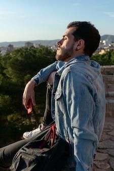 キャップとジャケットを持つ若い男は街を探しています。ライフスタイルのコンセプト、モデル。