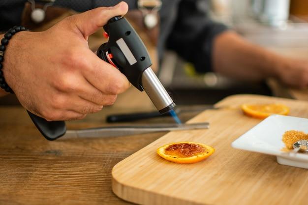 バーテンダーはカクテルを準備するためのバーでガストーチでオレンジを燃やす