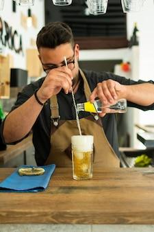 Бармен в пабе или ресторане готовит джин тоник коктейль.