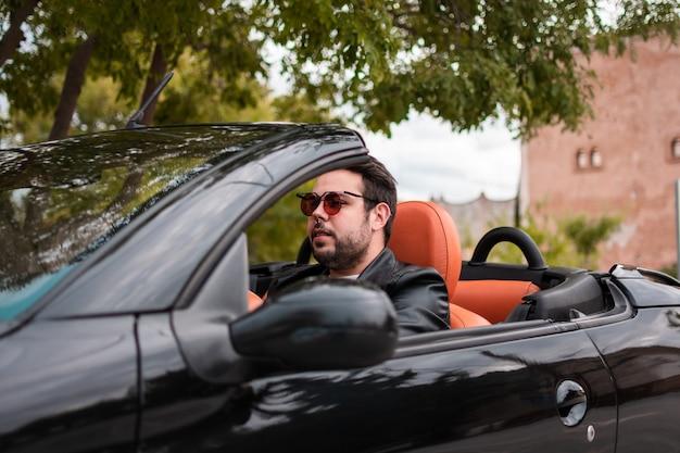 若い男がコンバーチブルを運転します。