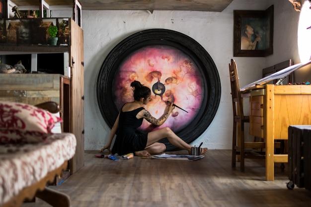 画家は床に横たわって彼女の素晴らしい絵を仕上げます
