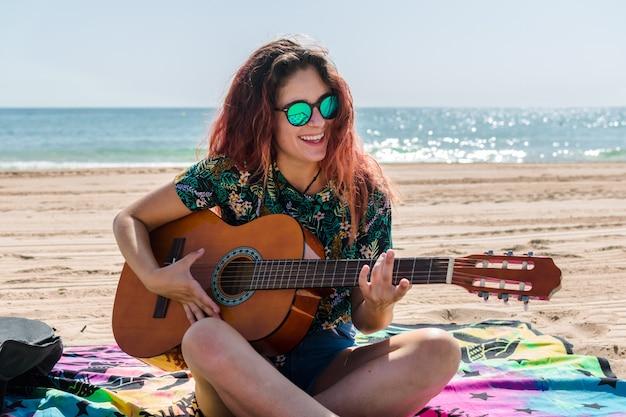 ビーチでギターを弾く若い女性