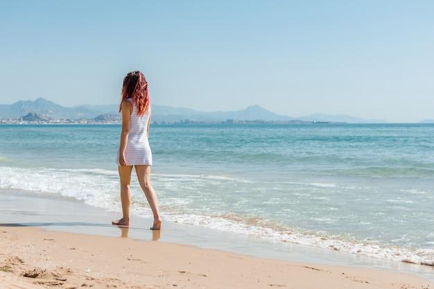 若い女性は白いドレスを着てビーチの上を歩く