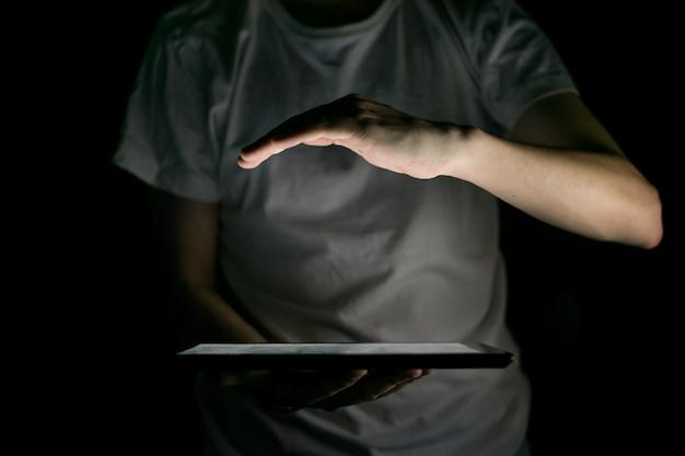 タブレットの光に照らされた手