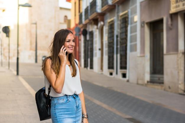 若い女性は通りで彼女のスマートフォンを使用しています