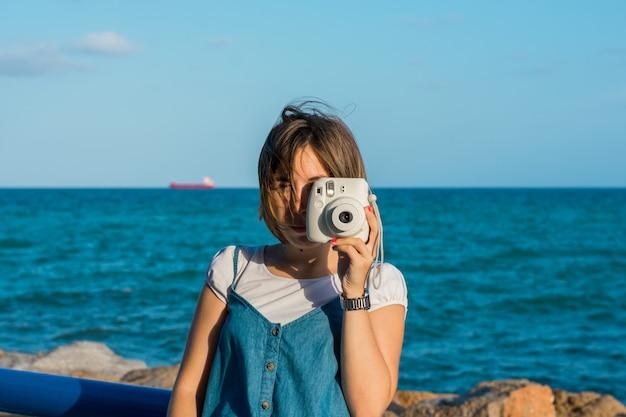 海岸でインスタントカメラを持つ若い女性