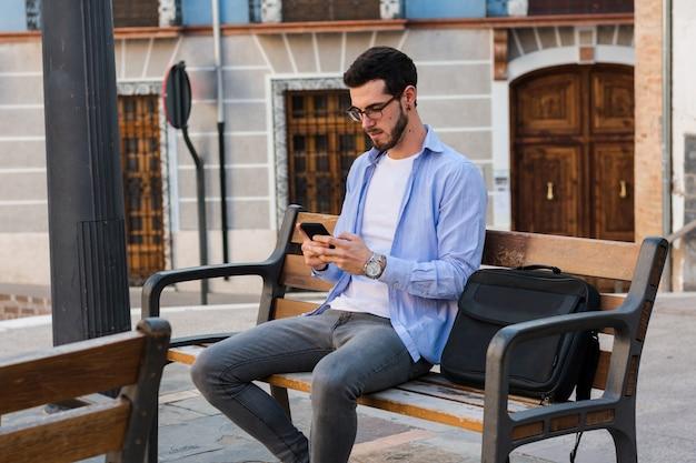 Молодой бизнесмен сидит на скамейке, в то время как он разговаривает по мобильному телефону