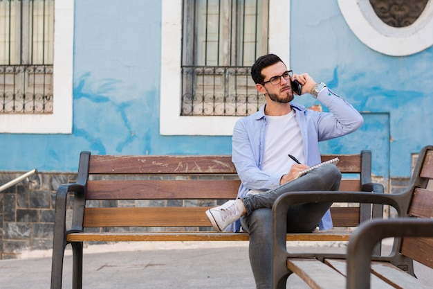 Молодой бизнесмен сидит на скамейке, в то время как он разговаривает по мобильному телефону и пишет в своей записной книжке