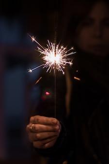 夜に女性の手が線香花火を持っています。