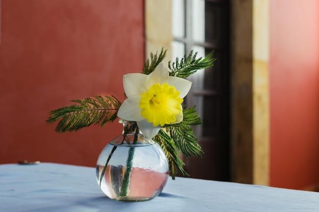 白い布のテーブルクロスの上のフラワーアレンジメント。水仙とガラスの花瓶の目玉。エレガントなビンテージレストランの背景