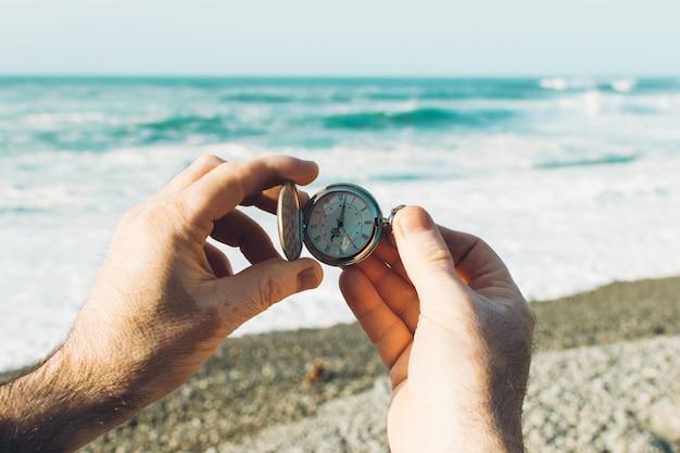 白斑の肌。男の手が懐中時計を保持しています。ビーチの背景。時間の概念休日の終わり
