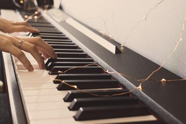 Женщина руки играет на пианино. фон клавиатуры. международный день джаза.