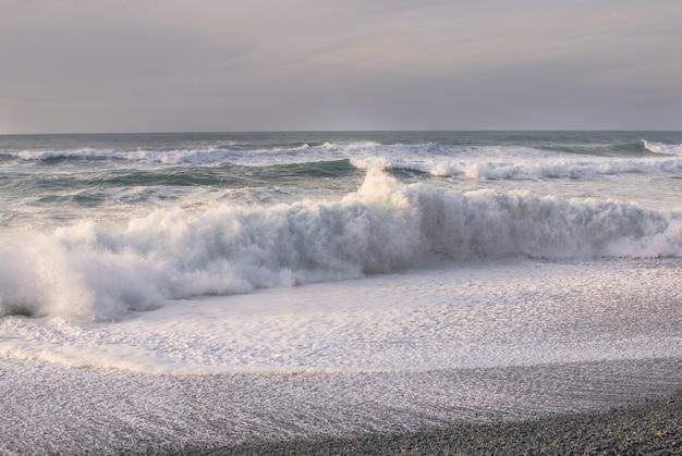 波とビーチで泡。荒れた日に光を沈めます。海の背景