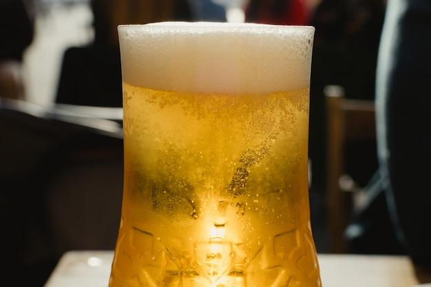 Пинта разливного пива на террасе. золотой прозрачный пузырьковый напиток