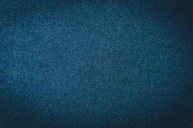 青いデニムのテクスチャ背景。インディゴテキスタイルジーンズ