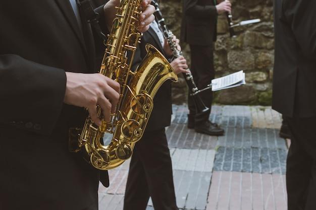 通りでサクソとオーボエを演奏するミュージシャン