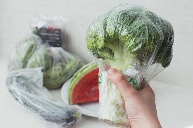 プラスチックのない果物と野菜の動きの概念。プラスチック包装とブロッコリーのパイを持っている手