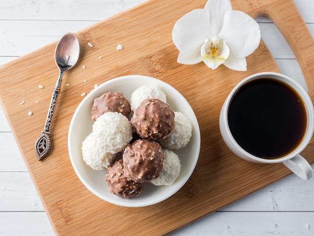 Шоколадно-кокосовые конфеты в миске на деревянном подносе кофейная чашка орхидея