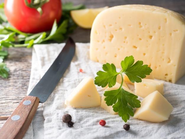 パセリ、リネンタオルの上のトマトとチーズの素朴な木製の背景。