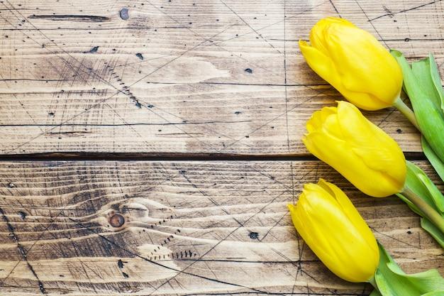コピースペースを持つ木製の背景に明るい黄色のチューリップ。