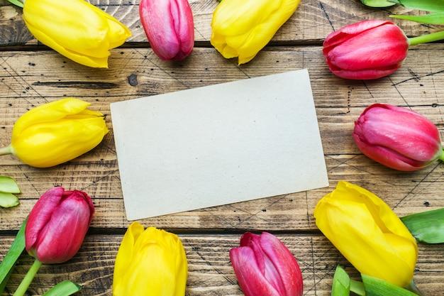 木製の背景に黄色とピンクのチューリップの花束。
