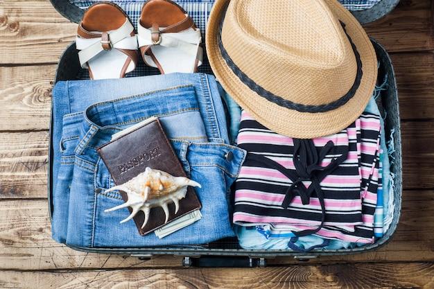 スーツケース、服、アクセサリー、古い木製のテーブルの上で旅行準備コンセプト。コピースペース