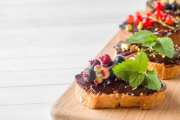 木製のサービングボードにチョコレートペースト、ピスタチオナッツ、新鮮な果実のサンドイッチ。コピースペース