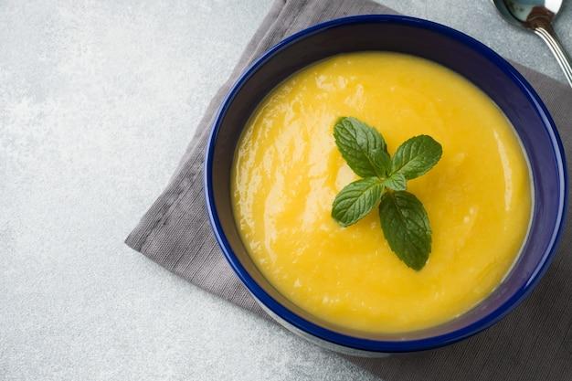 カボチャのスープは、テーブルの上の青い皿にスパイスとマッシュポテト。