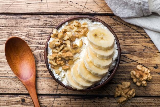 健康的な朝食。バナナとクルミの木製の背景にカッテージチーズ。