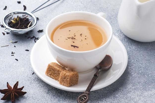 Чашка чая с молоком, коричневый анисовый сахар на сером столе.